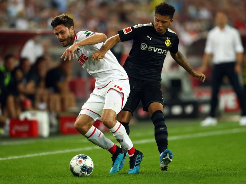 Köln v Dortmund - Jonas Hector of 1. FC Koeln holds off Jadon Sancho of Borussia Dortmund during the Bundesliga match between 1. FC Koeln and Borussia Dortmund at RheinEnergieStadion on August 23, 2019 in Cologne, Germany. (Photo by Lars Baron/Bongarts/Getty Images)