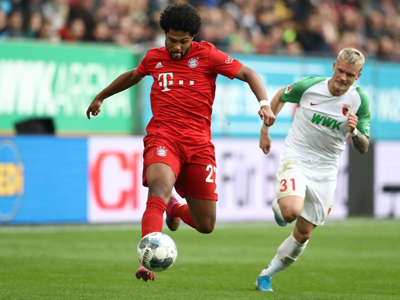 Augsburg v Bayern Munich - Serge Gnabry of FC Bayern Munich runs with the ball past Philipp Max of FC Augsburg during the Bundesliga match between FC Augsburg and FC Bayern Muenchen at WWK-Arena on October 19, 2019 in Augsburg, Germany. (Photo by Alexander Hassenstein/Bongarts/Getty Images)