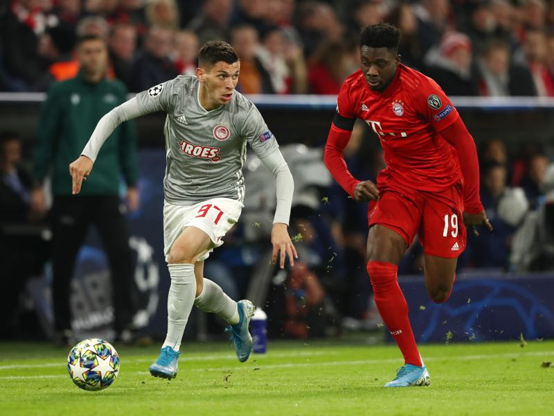 Bayern Munich v Olympiacos - Lazar Randjelovic of Olympiacos battles for possession with Alphonso Davies of FC Bayern Munich during the UEFA Champions League group B match between Bayern Muenchen and Olympiacos FC at Allianz Arena on November 06, 2019 in Munich, Germany. (Photo by Alexander Hassenstein/Bongarts/Getty Images)