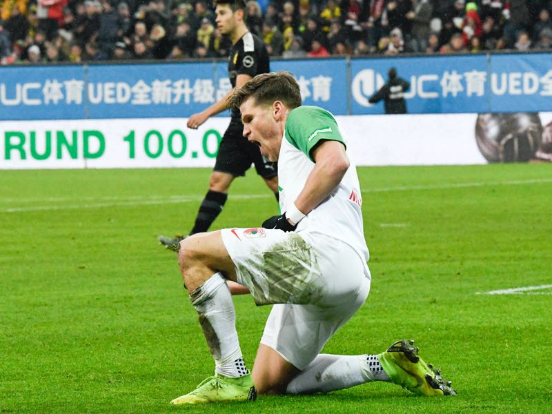 Augsburg v Dortmund - Augsburg's German forward Florian Niederlechner (C) reacts after he scored the 1-0 past Dortmund's Swiss goalkeeper Roman Buerki and German defender Mats Hummels (L) during the German first division Bundesliga football match Augsburg v Borussia Dortmund in Augsburg, on January 18, 2020. (Photo by THOMAS KIENZLE / AFP)