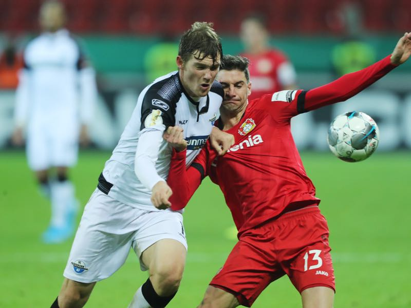 (L-R) Luca Kilian of Paderborn challenges Lucas Alario of Leverkusen during the DFB Cup second round match between Bayer Leverkusen and SC Paderborn 07 at BayArena on October 29, 2019 in Leverkusen, Germany. (Photo by Christof Koepsel/Bongarts/Getty Images)