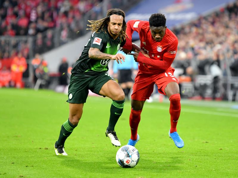 Bayern Munich v Wolfsburg - Alphonso Davies of FC Bayern Munich battles for possession with Kevin Mbabu of VfL Wolfsburg during the Bundesliga match between FC Bayern Muenchen and VfL Wolfsburg at Allianz Arena on December 21, 2019 in Munich, Germany. (Photo by Sebastian Widmann/Bongarts/Getty Images)
